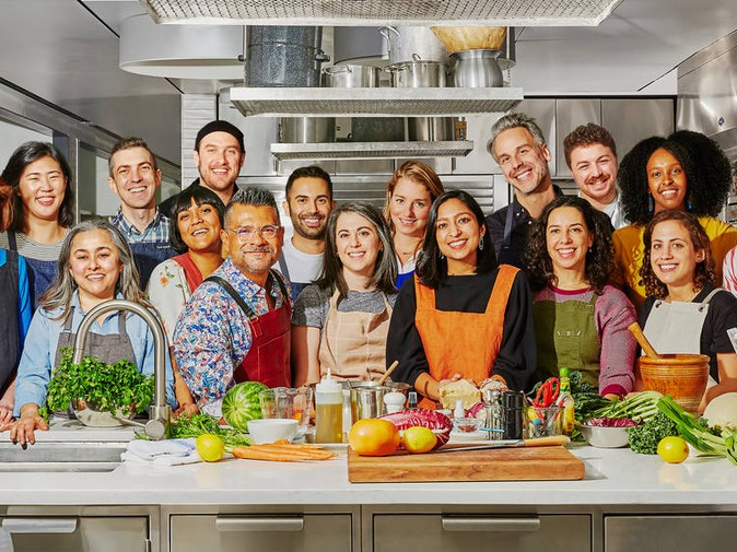 The team from the Bon Appétit test kitchen are stood smiling behind a kitchen counter that is laid with fresh fruit and veg