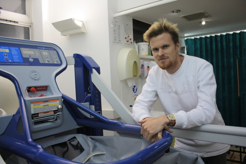 Zane Robertson leaning on an Alter-G machine