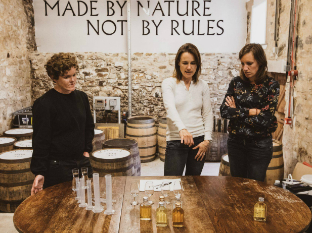 Three women stand in the distillery next to barrels, looking at samples of whiskey. Behind them is a sign that reads Made By Nature Not By Rules.