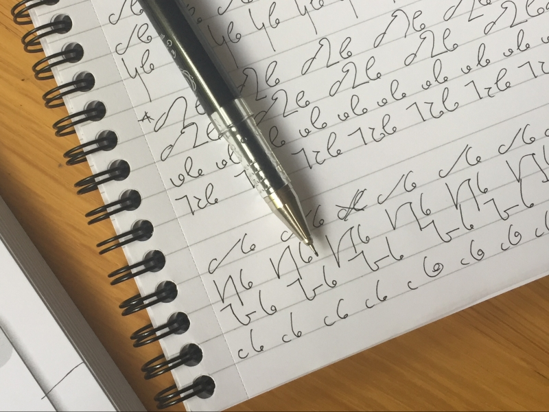 A notepad is on a wooden table and has a pen resting on top of it. On the pages there are lots of shorthand notes. On the left hand side of the photo is the corner of the shorthand exercise book.