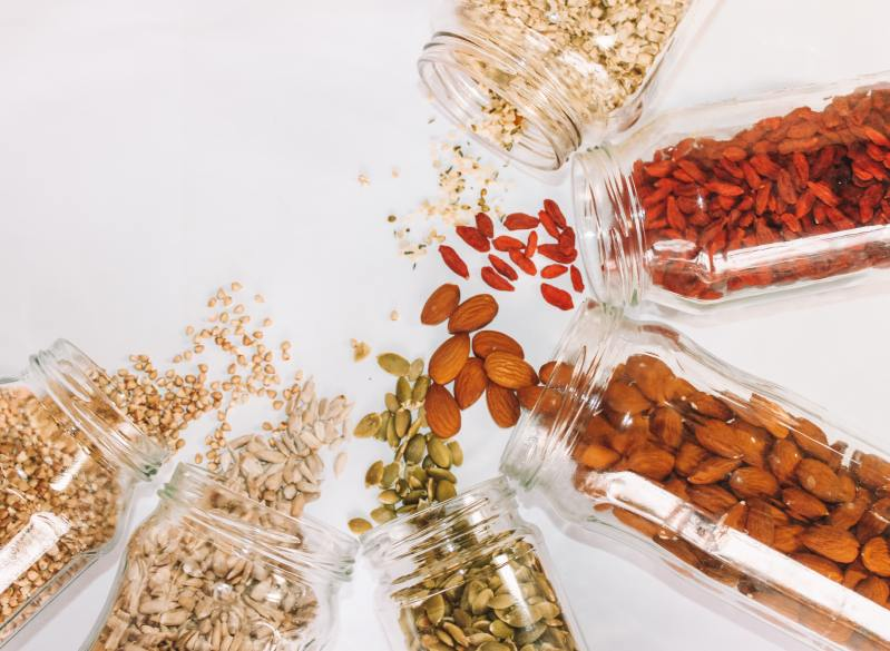 Six glass jars containing nuts and seeds are laid down on a white background, with some of the contents spilling out. Photo by Maddi Bazzocco on Unsplash